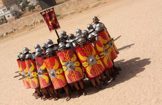 Roman Army reenactors holding shields in a protective formation.