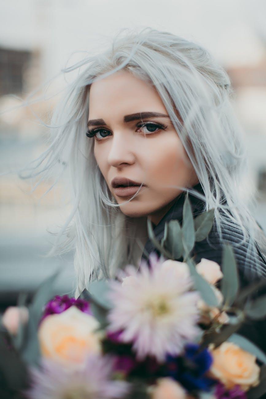 woman carrying flowers closeup photo