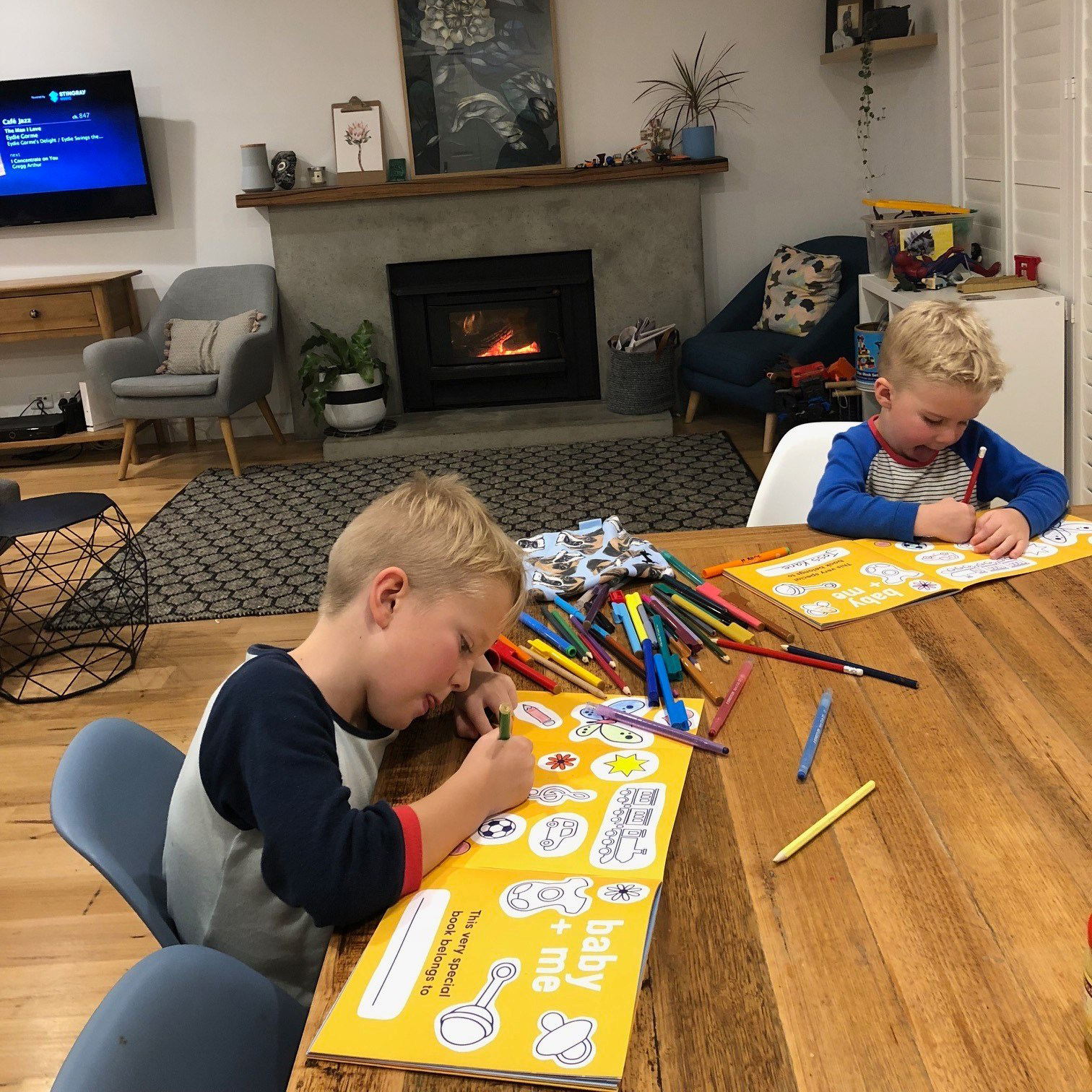 An image of children completing a page of the baby + me book, a book for older siblings. baby + me is in a unique format, with space for the child to write and to draw