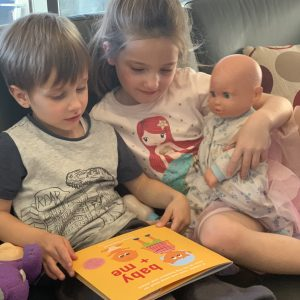 Picture of children reading the baby + me book, a unique book for soon to be big brothers and sisters