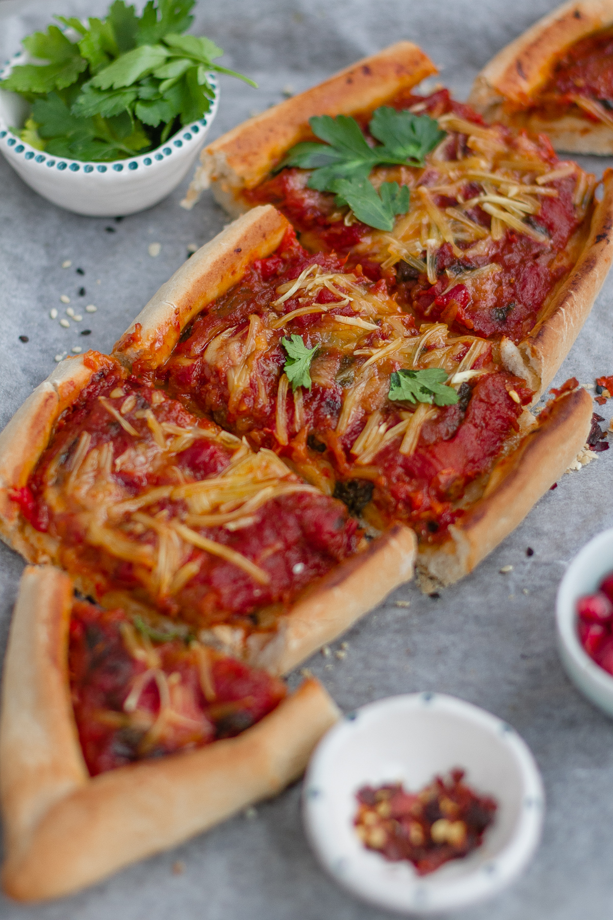 Spiced aubergine, tomato and red pepper vegan sliced pide (turkish flat bread) with pomegranate, parsley and chilli flakes