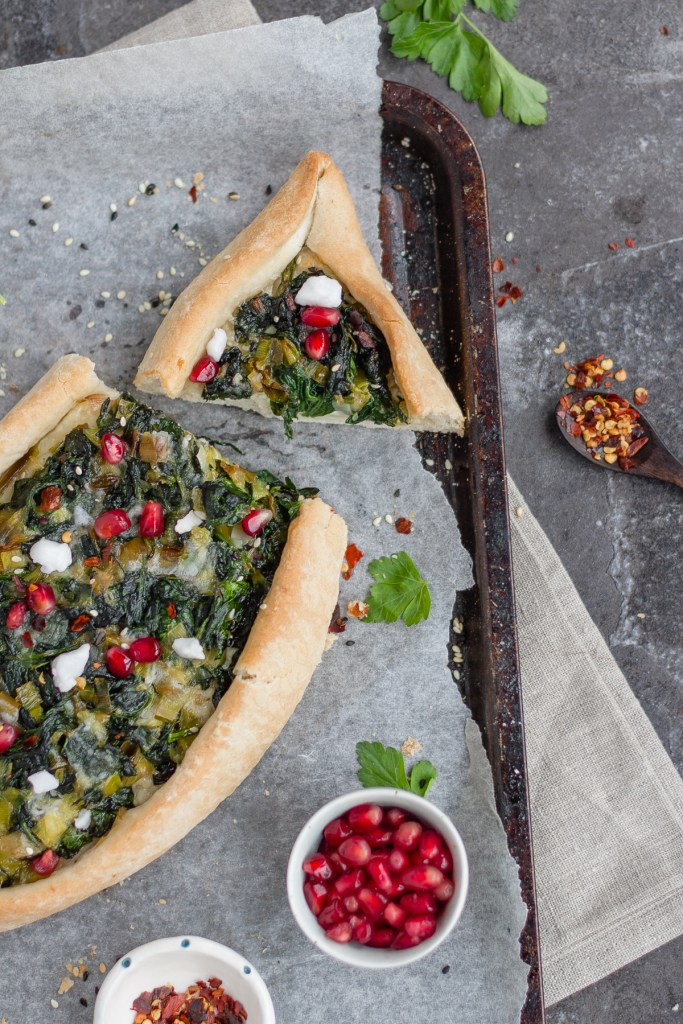 Sliced spinach, leek and vegan feta pide with pomegranate and chilli flakes