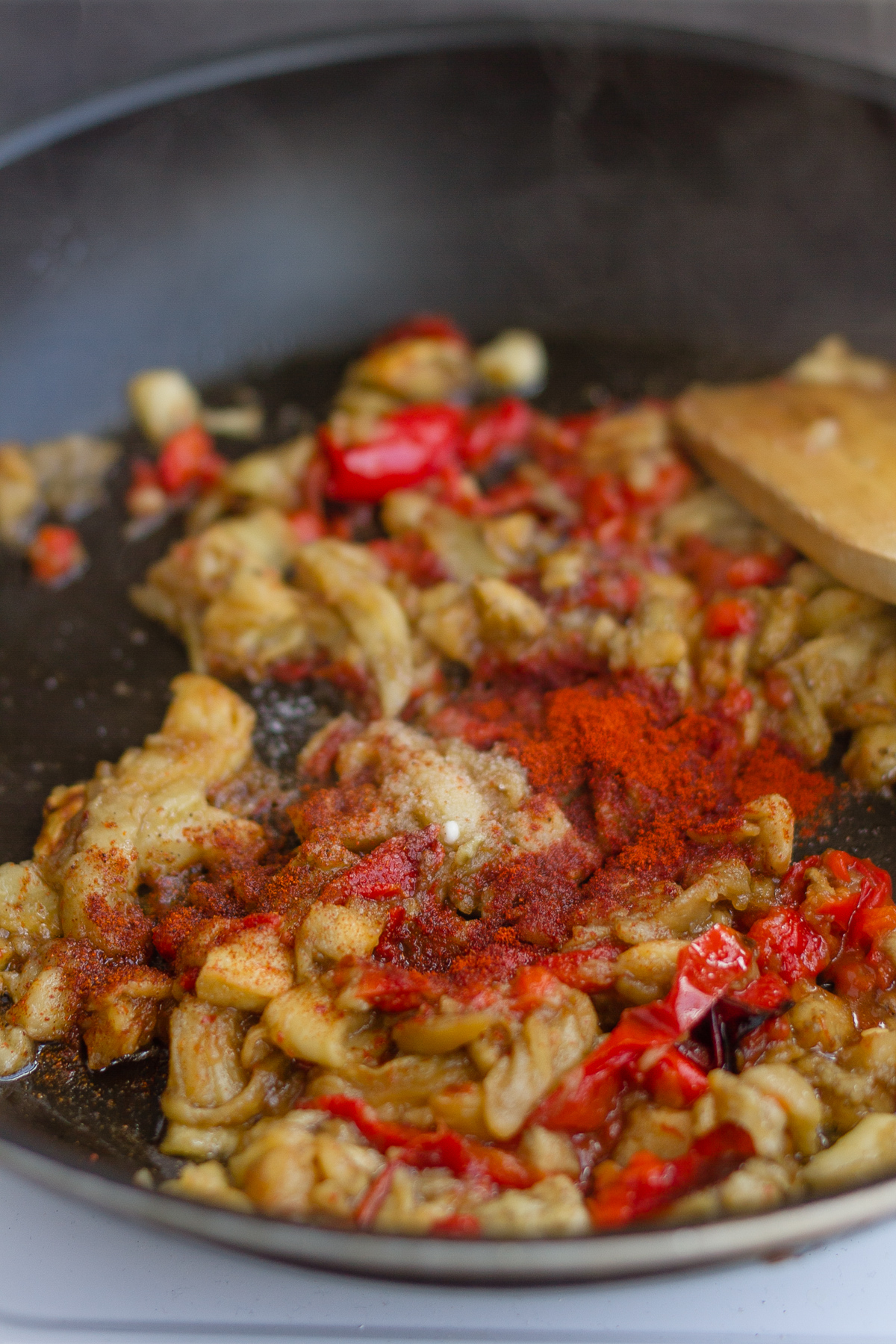 adding seasoning to the frying pan with the aubergine and red pepper