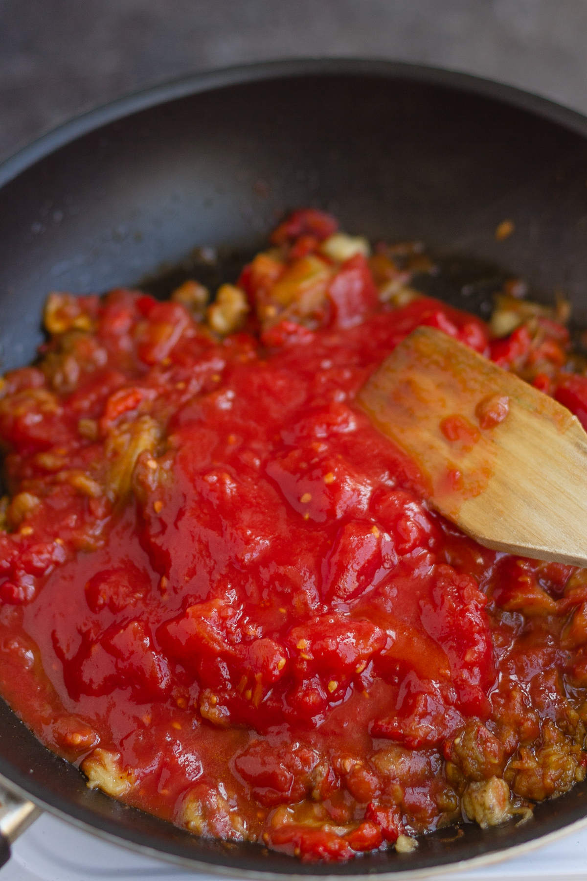 adding mashed plum tomatoes to pan with aubergine and red pepper