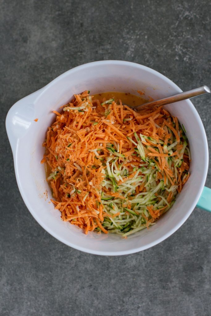 mixing courgette and sweet potato in large bowl with eggs