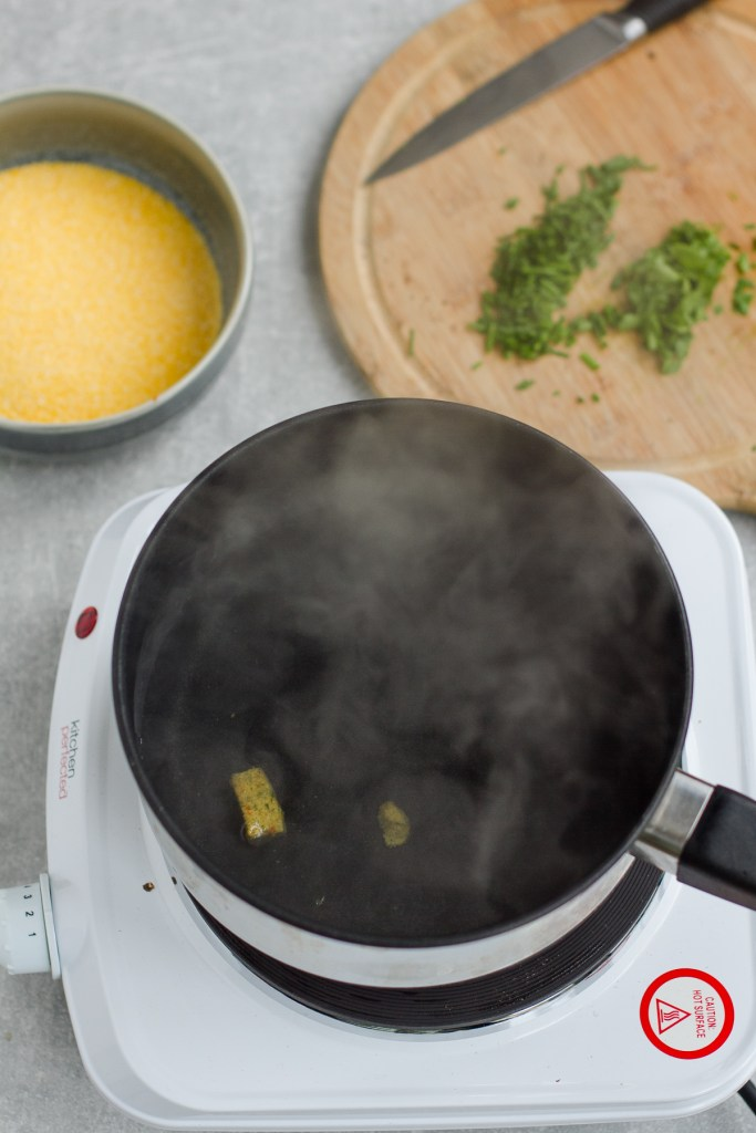 adding stock tablet to small pan with water