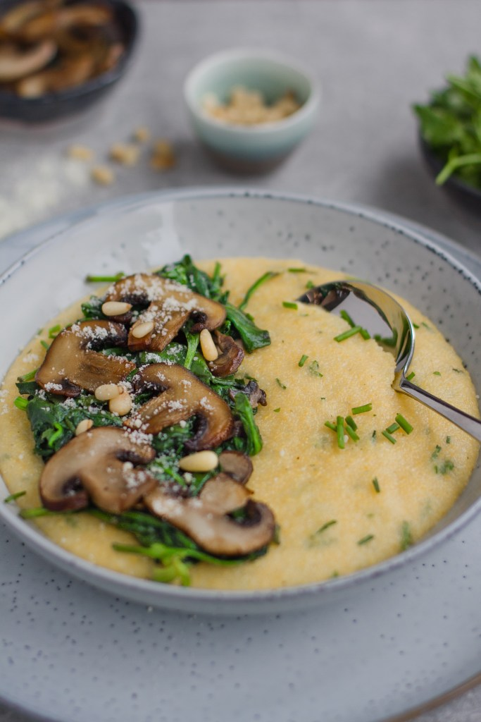 simple herby cauliflower cheese polenta topped with sauteed mushrooms, spinach and pine nuts