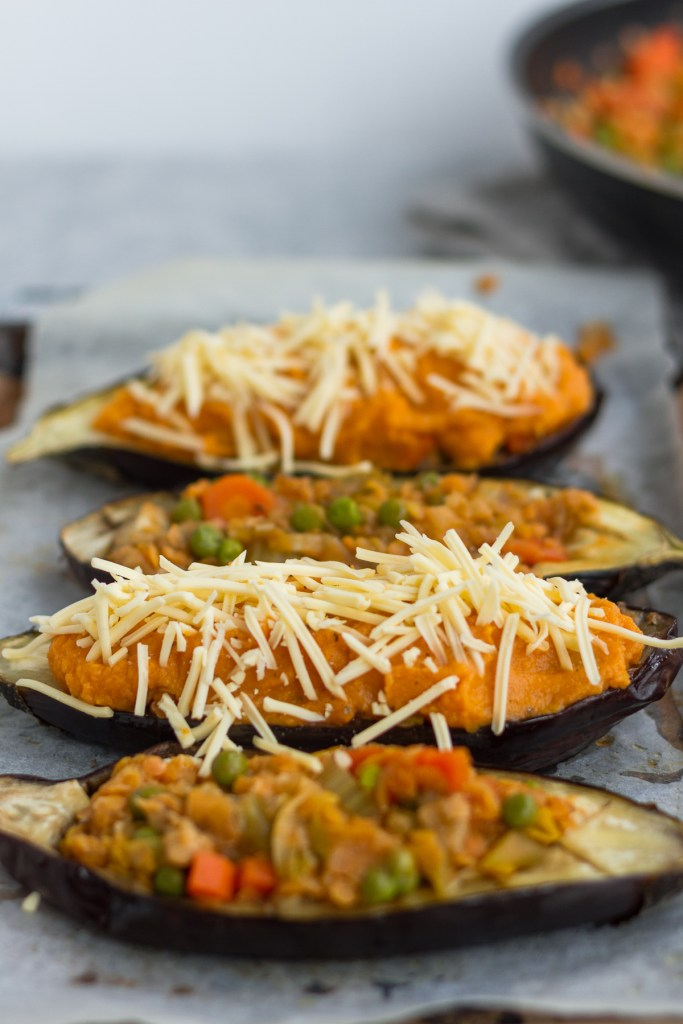 stuffed aubergine with lentil shepherds pie filling and topped with sweet potato mash. sprinkled with violife cheese