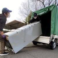 冷蔵庫をトラックに積み込んでいる女性の画像
