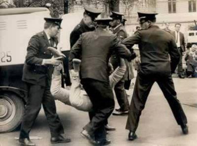 """Integrantes da extinta Guarda Civil, com viatura da Rádio Patrulha ao lado, """"camburão"""" com """"chiqueirnho"""" de porta aberta, conduzindo coercitivamente um fora da lei, na década de 60."""