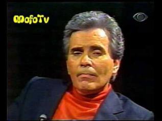 """Jacinto Figueira Júnior, """" O Homem do Sapato Branco"""" nasceu em 27 de dezembro de 2005. Foi um apresentador de televisão brasileiro conhecido como Nos anos 50, fez sucesso no meio musical com sua banda country """"Junior e seus Cowboys"""", mas só ingressou na TV em 1963, com o programa """"Fato em Foco"""", transmitido pela TV Cultura e um ano depois com """"Câmera Indiscreta"""", na mesma emissora. Ainda passou pela Rádio Nacional de São Paulo (atual Rádio Globo) nos anos 1960 e 1970. Nessa época gravou a música """"O Charreteiro"""", que fez sucesso graças ao programa de rádio de Silvio Santos, que a tocava diariamente e que chegou a lhe conceder uma medalha de ouro no quadro """"Sobe e Desce"""", no qual os ouvintes opinavam se a música deveria continuar a ser tocada (sobe) ou devia ser substituída por outro sucesso (desce). Esse sucesso como cantor o fez até participar de uma telenovela e de uma fotonovela, publicada numa revista para o público feminino nos anos 60. No seu próprio programa de rádio na Rádio Nacional (depois Rádio Globo), havia um quadro com dramatizações radiofônicas. Mas o que levou a se tornar conhecido nacionalmente e considerado um precursor foi seu programa """"O Homem do Sapato Branco"""", que criou em 1966 pela Globo, que passou para a Televisão e logo foi interrompido devido a problemas com a ditadura militar. Depois retornaria já nos anos 80, sendo transmitido pelas emissoras Bandeirantes, Globo, Record e SBT. Costumava entrevistar seus convidados usando um sapato branco, que sempre era focalizado pelas câmeras. A idéia de usar os sapatos brancos surgiu porque era a cor dos sapatos que os médicos e os psiquiatras usavam, e Jacinto pretendia ser uma espécie de """"médico"""" do povo em seus programas. Jacinto Figueira Júnior foi o introdutor do estilo """"mundo cão"""" na televisão brasileira.[carece de fontes] Ele trazia para o palco casais com problemas e que chegavam a brigar na frente das câmeras. A transmissão de programas policiais de apelo popular, foi depois adotado ainda nos """