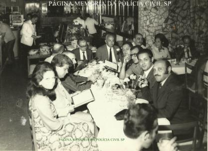 Delegado de Polícia Coriolano Nogueira Cobra, ao fundo na mesa principal, ao lado do delegado de óculos, de terno cinza e gravata preta, em restaurante com outros delegados e familiares, na década de 60. (acervo da filha, Teresa Cobra).