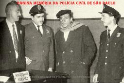 O saudoso compositor e cantor Adoniran Barbosa em visita à Central de Polícia da 1ª Delegacia Auxiliar (atual DECAP), no Pátio do Colégio, ladeado com o Investigador de serviço e dois integrantes da extinta Guarda Civil da Polícia do Estado de São Paulo, em 1.961.