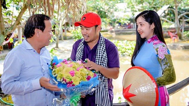 Anh Phong tặng hoa thắt bằng lá dừa cho đại diện khách du lịch.