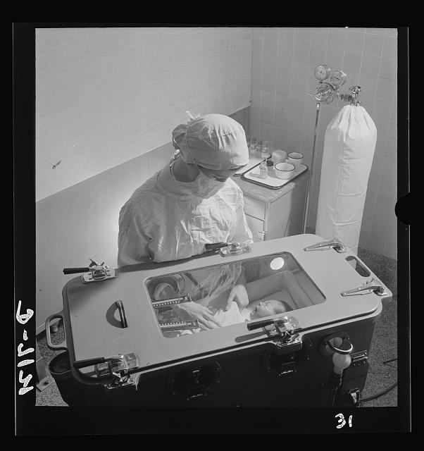 Nurse training. Care of prematurely born babies is one of the most complicated procedures which must be learned by the student nurse. Feeding, bathing and diaper changing are carried on inside the incubator, in which temperature, humidity and oxygen must be carefully regulated. The oxygen tank can be seen in the background.  1942 November.  Fritz Henle, photographer.  (Library of Congress)