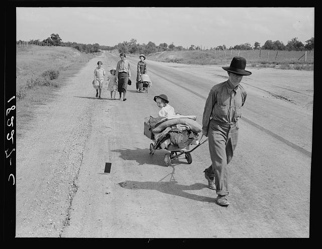 Family walking on highway, five children. Started from Idabel, Oklahoma. Bound for Krebs, Oklahoma. Pittsburg County, Oklahoma. In 1936 the father farmed on thirds and fourths at Eagleton, McCurtain County, Oklahoma. Was taken sick with pneumonia and lost farm. Unable to get work on Work Prjects Administration and refused county relief in county of fifteen years residence because of temporary residence in another county after his illness.  1938 June.  Dorothea Lange, Farm Security Administration photographer (Library of Congress)