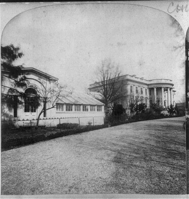 White House, with conservatory in foreground, executive office buildings present site, 1869.