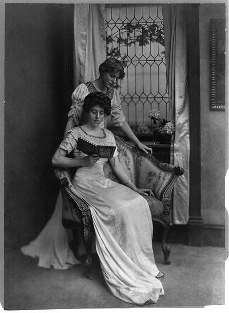 Miss Jessie Wilson, standing, and Miss Eleanor R. Wilson, seated, reading.  c. 1912