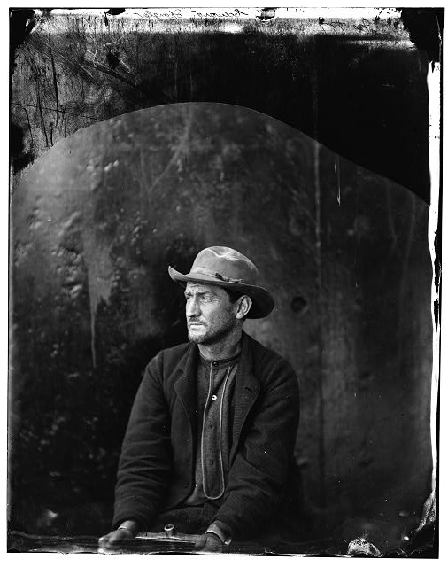 Washington Navy Yard, D.C. Edman Spangler, a conspirator, in hat and manacled.  April 1865