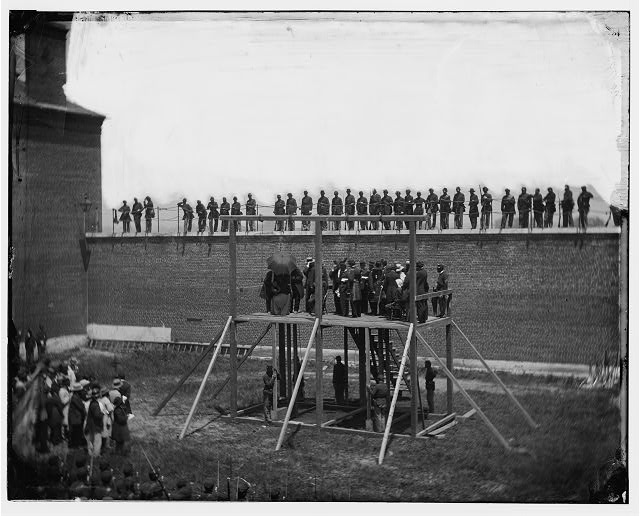 Washington, D.C. The four condemned conspirators (Mrs. Surratt, Payne, Herold, Atzerodt), with officers and others on the scaffold; guards on the wall.  1865 July 7.  Alexander Gardner, photographer.