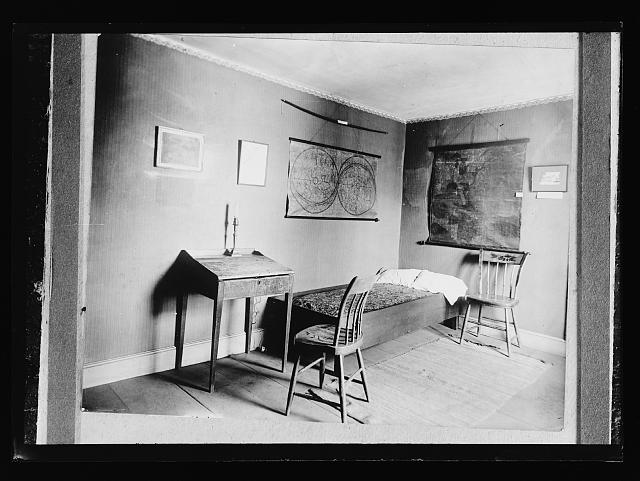 Bedroom with maps on wall, possibly in historic house or museum.  (Between 1910 and 1930)