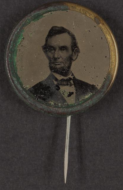 Political campaign button for 1864 presidential election showing bust portrait of Abraham Lincoln, facing left (Anthony Berger photo Feb. 9, 1864); metal casing with pin fastener attached.