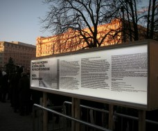 "A sunlit infamous Lubyanka behind an exhibit that reads: ""Places of Repression in Moscow"""