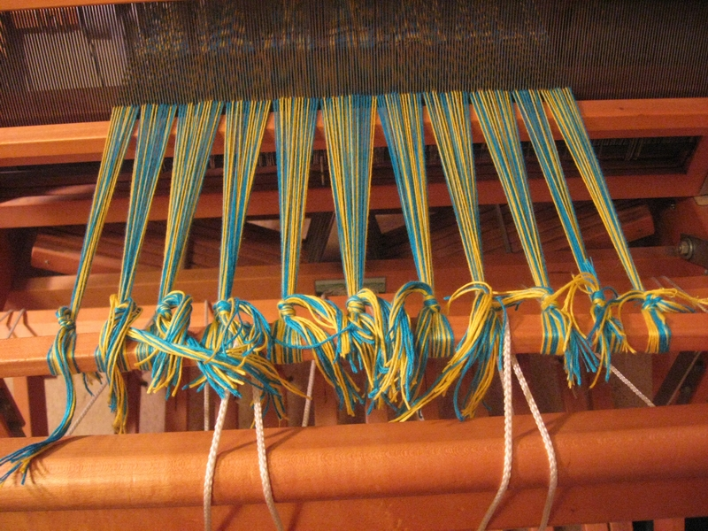 Front ends of the warp are cut and tied onto the front apron bar.