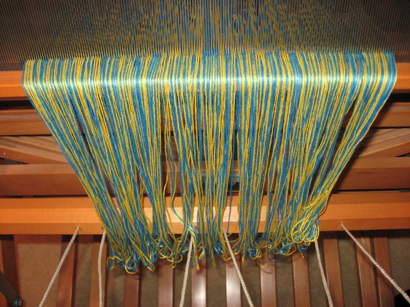 After the entire warp is wound onto the back beam, the front of the warp hangs loosely from the reed at the front of the loom