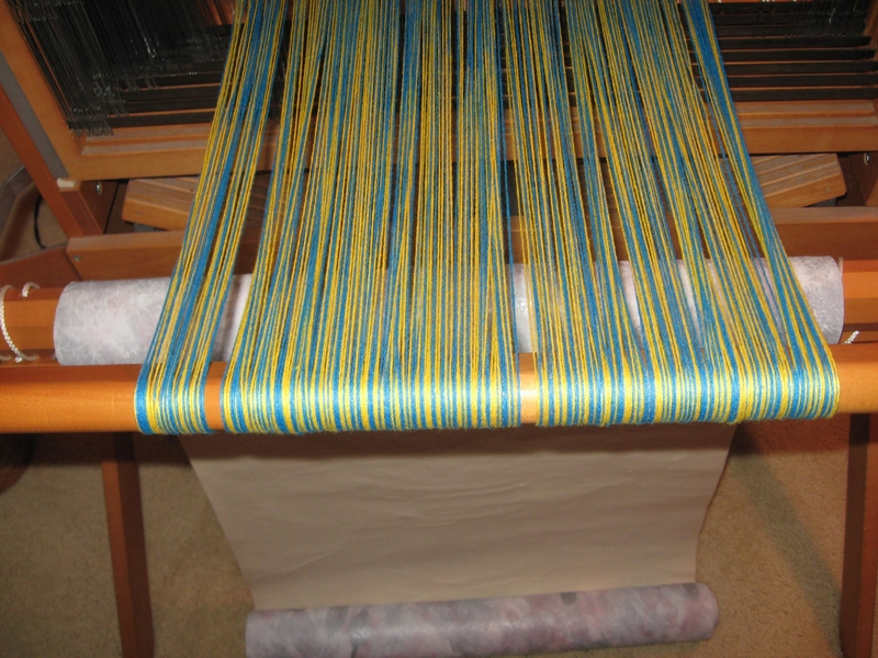 Warp is wound onto the back beam using a roll of wallpaper between layers to maintain tension.