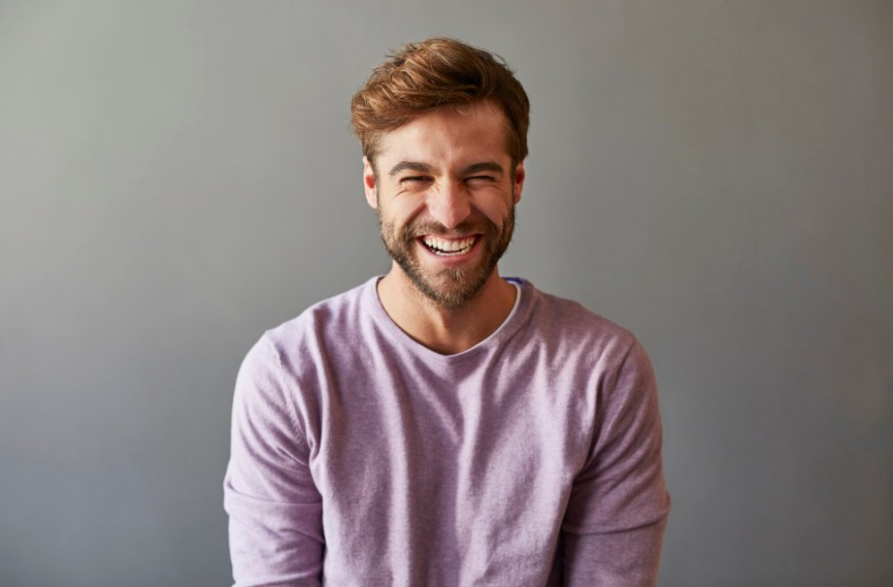 Professional laughing over gray background