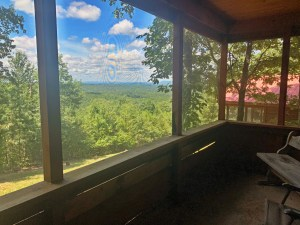 Mountain view from screened in porch of rustic mountainside cabin