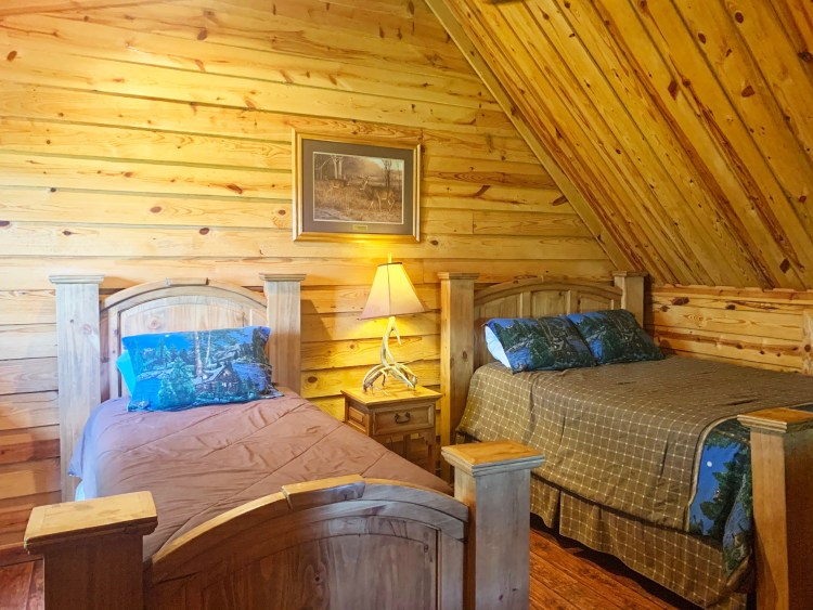 Loft bedroom with beds in rustic two-story cabin