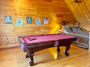 Pool table and bed in loft of rustic two story cabin