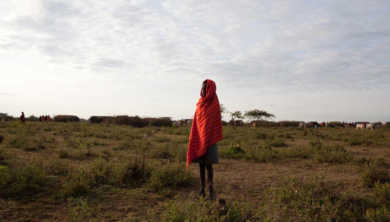 Marcy Mendelson, The Samburu Story | A Samburu boy warms himself by the light of the rising sun. Outside Kisima, Samburu County, Kenya.  August 22, 2013.