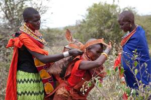 Marcy Mendelson, The Samburu Story | After hours of butchering the ritually slaughtered cows, the women pack and carry the meat in heavy sacks strapped across their head and balanced on their backs. They return to the grand manyatta to prepare the feast.