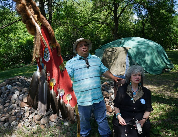 Tommy Tomahawk, tribal relations, and Mendota Mdewakanton Dakota Tribal Community chairperson Sharon Lennartson sat in the shade in front of a sweat lodge for a portrait.