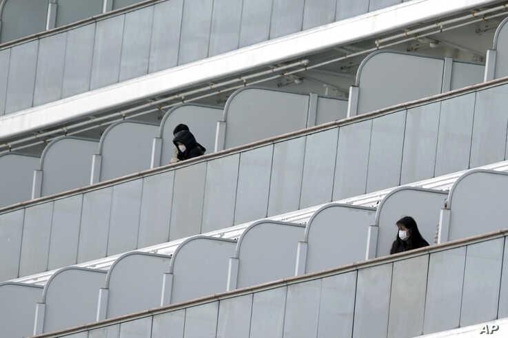 Masked passengers stand outside on the balcony of the cruise ship Diamond Princess anchored at Yokohama Port in Yokohama, near…