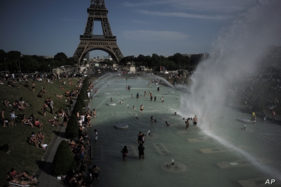 People cool off in the fountains of the Trocadero gardens, in front of the Eiffel Tower, in Paris, June 28, 2019.