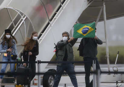 Brazilians hold a Brazilian flag after arriving from Wuhan, China, the epicenter of the coronavirus at the Annapolis Air Force Base, in Anapolis city, Goias state, Brazil, Feb. 9, 2020.