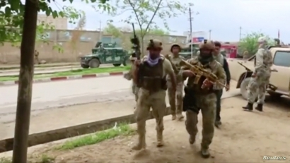 Afghan security personnel walk on a street in Kunduz, Afghanistan, Aug. 31, 2019, in a still image taken from video.