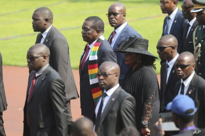 Zimbabwean President Emmerson Mnangagwa pays his respects to former Zimbabwean leader Robert Mugabe, at the National Sports stadium during a funeral ceremony in Harare, Sept, 14, 2019.