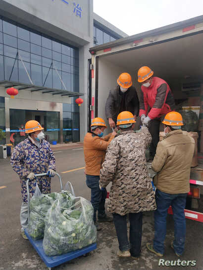 Construction workers of a temporary hospital receive meat and vegetables delivered by Wuhan resident Chen Hui and another…