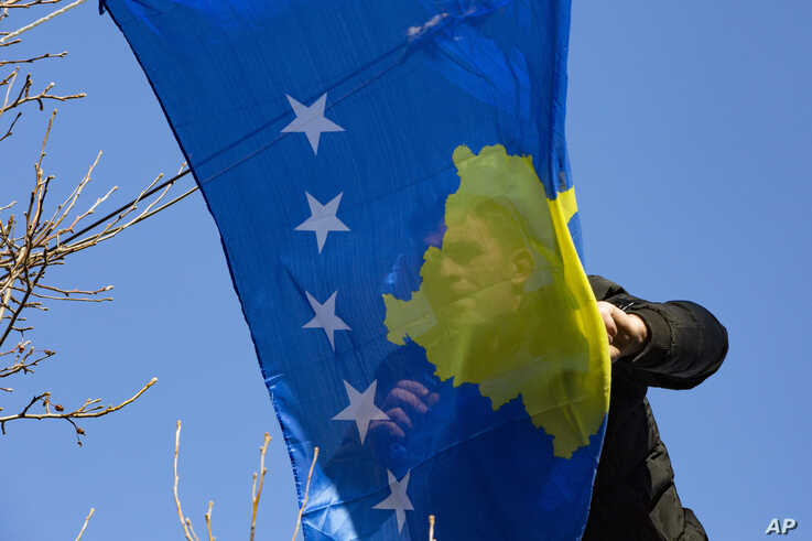 A municipality worker hangs Kosovo's flag to decorate the main street, during the 12th anniversary of the country's…