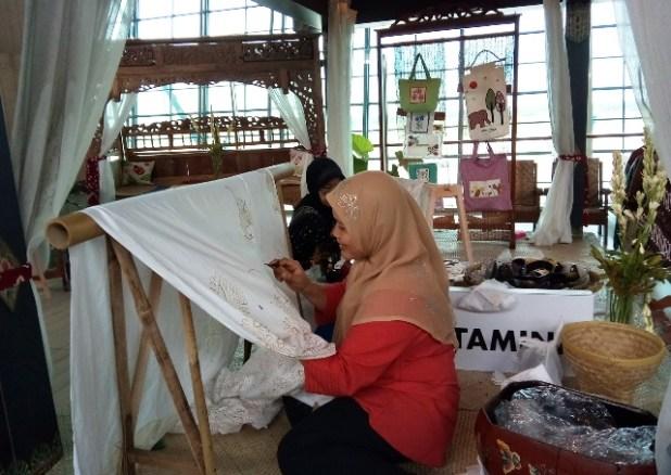 Belajar membatik di stand Batik binaan Pertamina di areal ruang tunggu keberangkatan. Foto by menixnews.com