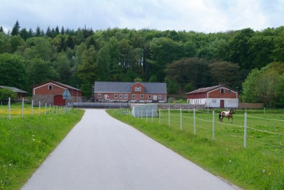 Moselundsgård set fra P-pladsen ved jernbaneoverskæringen. Den tværgående vej, der ses i baggrunden forbinder Engesvang og Funder.