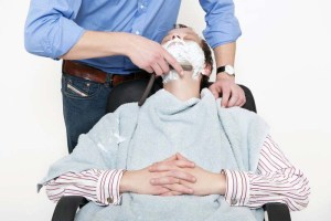 Man receiving a hot towel shave by a barber
