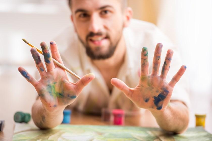 Mann mit ausgestreckten bemalten Händen