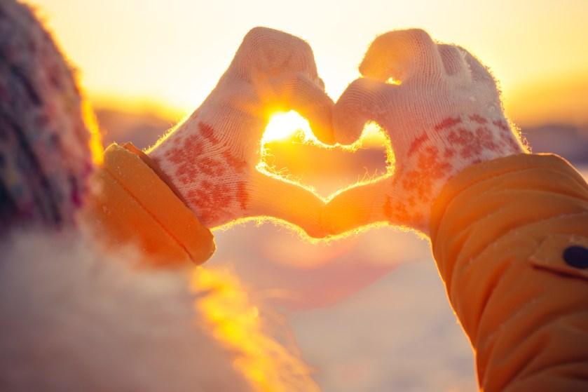 Bild einer behandschuhten Hand formt ein Herz vor der Wintersonne