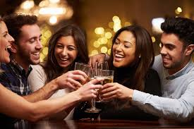 Coloured photo of 2 male and 3 female friends, hugging and holding drinks like they're saying cheers.